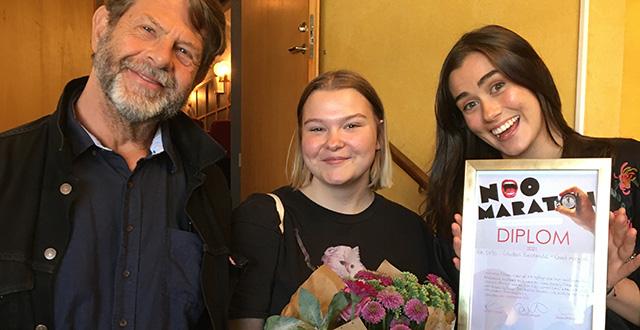 Tre personer som ler och håller i ett diplom och en blombukett.